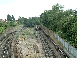 Newbury Park tube station - Looking south from Eastern Avenue towards the former alignment leading to Ilford, with the current alignment diverging either side and burrowing underground which heads westwards to Gants Hill and the city.