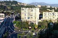 Vue d'un immeuble en ville contourné par une bretelle de voie rapide menant vers un tunnel sous une colline boisée.