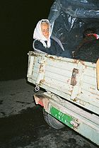 An elderly woman sitting in the back of a utility trailer