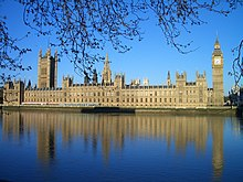 The[깨진 링크(과거 내용 찾기)] Houses of Parliament in London, seen across the river, are a large Victorian Gothic building with two big towers and many pinnacles