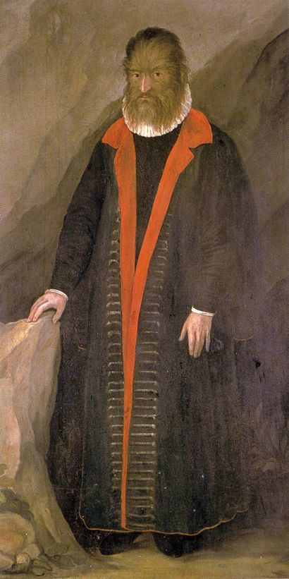Painted portrait of Petrus Gonsalvus, who likely had Hypertrichosis.  His face is entirely covered in hair, he is wearing a nearly floor-length dark (black or brown) coat with a red lining, partially open over what looks to be a black shirt or doublet with a white ruffled collar.