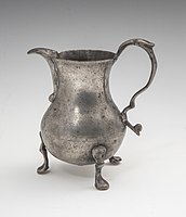 An ornate pewter cream pitcher