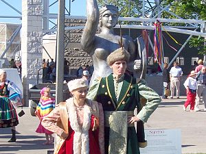 Polish Fest - A costumed couple pose in front of Syrena the Warsaw mermaid