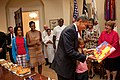 President Barack Obama, with daughter Sasha, looks at the card given to him during a birthday party with his staff in the Roosevelt Room of the White House.jpg