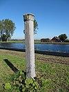 foto van Hardstenen grenspaal voor de markering van de gemeentegrens, voorzien met het wapen van Delft