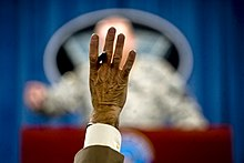 Reporter raising hand at US Army press conference.jpg