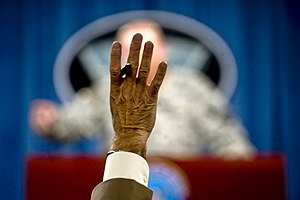 A reporter raises his hand to ask a question a...