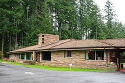Brown one-story  modern flagstone building, parking lot in front and fir trees behind it.