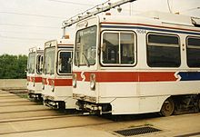 Three abreast white trolleys with a red stripe around the vehicle ends.