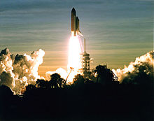 A space shuttle launches into a dawn sky. Clouds in the sky, in the launch plume and from the flame trench, are visible, as is the scaffolding-like launchpad and some vegetation silhouetted in the foreground.