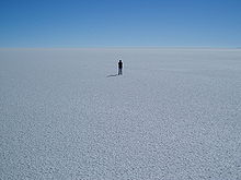 A panorama of flat, white ground, stretching to the horizon; a single person stands in the middle of the frame in the distance