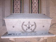 "A white marble coffin sits on a ledge in front of stained glass windows. On the front of the coffin is a large 5-pointed star. Engraved within the star are the words ""Texas Heroes"" and small images of three men."