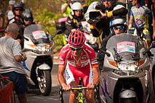 A road racing cyclist in his early thirties, wearing a predominantly red jersey with white trim and a red helmet. A motorcycle bearing a cameraman follows behind him, with a further caravan and other spectators in the background.