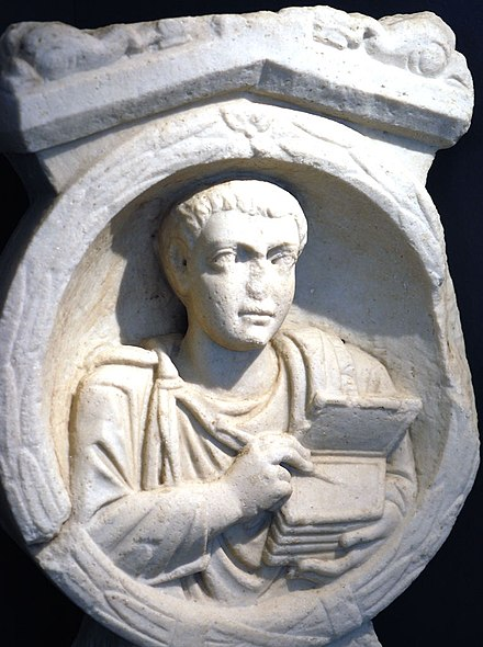 Roman scribe with his stylus and tablets on his tomb stele at Flavia Solva in Noricum. Scribe tomb relief Flavia Solva.jpg