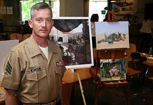 Kristopher Battles - Sgt. Battles stands in front of some of his paintings.