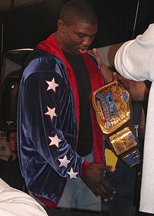 "An African American man is facing to the right and holding up a professional wrestling tag team championship, engraved with the words ""World Wrestling Entertainment Tag Team Champions"". He is wearing light blue jeans, a black t-shirt, and a dark blue jacket, with a red lining, and 5 white stars, outlined in red, are visible upon the left sleeve."