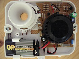 Smoke detector - Inside a basic ionization smoke detector. The black, round structure at the right is the ionization chamber. The white, round structure at the upper left is the piezoelectric horn that produces the alarm sound.
