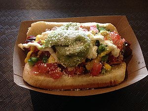 Sonoran hot dog - A Sonoran hot dog, with pinto beans, tomatoes, green salsa, jalapeño, mustard, and mayonnaise, and with avocado and cotija cheese on top