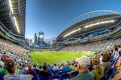 Uno stadio con un campo di calcio al crepuscolo.  Il livello inferiore è pieno di persone.