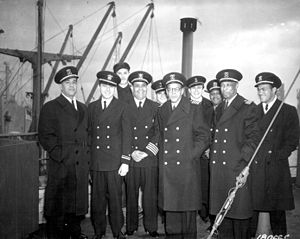 "SS Booker T. Washington - Captain and crew of the new Liberty Ship SS Booker T. Washington just after it completed its maiden voyage to England. (L-R) C. Lastic, Second Mate; T. J. Young, Midshipman; E. B. Hlubik, Midshipman; C. Blackman, Radio Operator; T. A. Smith, Chief Engineer; Hugh Mulzac, Captain of the ship; Adolphus Fokes, Chief Mate; Lt. H. Kruley; E. P. Rutland, Second Engineer; and H. E. Larson, Third Engineer."" Captain Hugh Mulzac is fourth from the left on the first row. 8 February 1943."