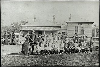Gowrie, New South Wales - Gowrie Public School in 1887. The two ladies near the fence in the background  are sisters, Mrs. Henry Whitten (née Elizabeth Mason) and Mrs. Alec Barthgate (née Grace Mason). The teacher is David Edward Rhind with his wife and baby. Most of the children, including the girls were  wearing  elastic-side boots which were the  fashion.