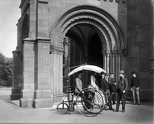 Copeland steam bicycle - Copeland carrying Frances Benjamin Johnston on his Phaeton Moto-Cycle at the Smithsonian Institution Building in 1888. Behind are his partner Sandford Northrop, and Smithsonian officials E. H. Hawley, W. H. Travis and J. Elfreth Watkins.