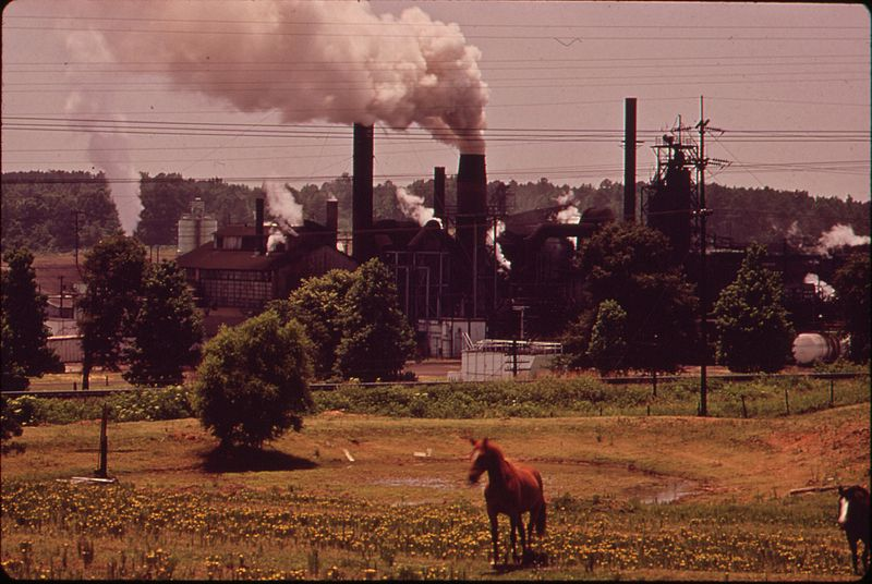 """File:THE ATLAS CHEMICAL COMPANY BELCHES SMOKE ACROSS PASTURE LAND IN FOREGROUND. THE PLANT IS REFERRED TO AS """"OLD DARKY""""... - NARA - 546130.jpg"""