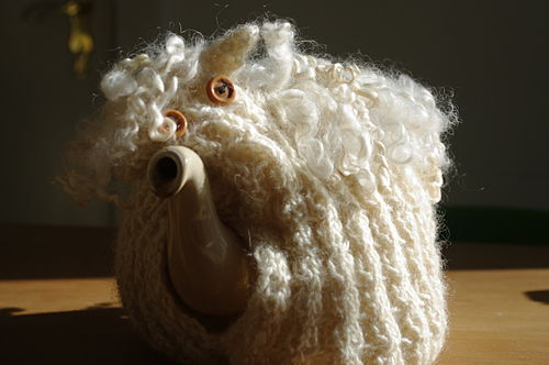 Tea pot with knitted tea cosy sheep