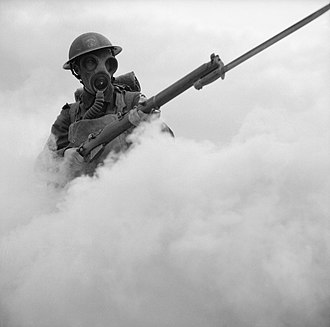 Royal Hampshire Regiment - Men of the 12th Battalion, Hampshire Regiment in training at Hengistbury Head near Bournemouth, Dorset. Wearing his gas mask, a soldier advances through a smoke screen.