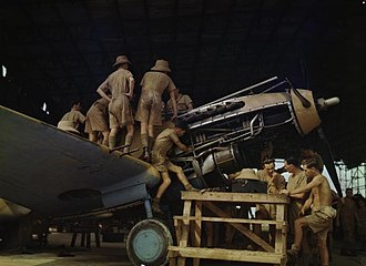 Sekondi-Takoradi - The Desert Air Force, 1943; Royal Air Force (RAF) airmen in tropical dress work on the Allison V-1710 Aircraft engine of a Tomahawk aircraft in a makeshift hangar. The photograph is believed to have been taken at RAF Takoradi.
