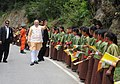 The Prime Minister, Shri Narendra Modi waving to children who lined up waving flags to wish him goodbye along the road to the airport, in Thimphu, Bhutan on June 16, 2014.jpg
