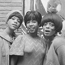 Black-and-white image of the Supremes smiling.