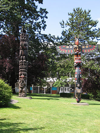 History of Canada - A Gitxsan Totem pole (left) and Kwakwaka'wakw Totem pole (right) at Thunderbird Park in Victoria, British Columbia, Canada.