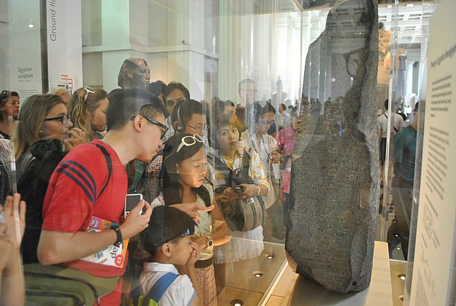 A crowd of visitors examining the Rosetta Stone at the British Museum Tourist watching Rosetta Stone at British Museum.JPG