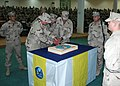 US Navy 050305-N-0577F-010 Steelworker Constructionman Michael Gilcrest and Chief Builder Andrew Sprague, the youngest and oldest Seabees in Fallujah, Iraq, cut a birthday cake.jpg