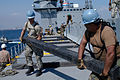 US Navy 070206-N-5291U-003 Pfc. Anthony Phillips, assigned to 567th Inlet Cargo Transportation Company, and Storekeeper 2nd Class Lawrence Gonzalez, assigned to Navy Cargo Handling Battalion 13, carry a wooden beam to support a.jpg