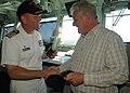 US Navy 090705-N-8487G-215 Capt. Gregory J. Fenton , commanding officer of the amphibious transport dock ship USS Denver (LPD 9), souvenir USS Denver ball cap and Zippo lighter.jpg