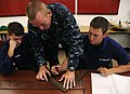 US Navy 100803-N-7498L-069 Chief Damage Controlman Tommy Thompson, an instructor assigned to the Center for Naval Engineering Learning Site, Pearl Harbor, demonstrates how to measure out K-type shoring angles.jpg