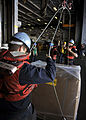 US Navy 100911-N-7103C-059 Seaman Kyle Smith, from Greenville, S.C., helps rig a cargo pallet to a sliding pad-eye during a replenishment at sea wi.jpg