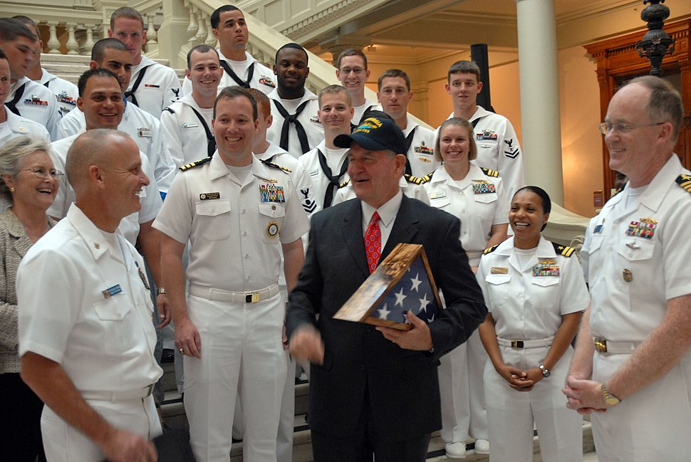 US Navy 101013-N-6736S-066 Georgia Gov. Sonny Perdue, center, is presented a command ball cap by Master Chief Richard Rose