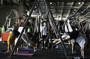 US Navy 120112-N-GC412-037 Sailors participate in a total resistance training (TRX) class in the hangar bay aboard the Nimitz-class aircraft carrie.jpg