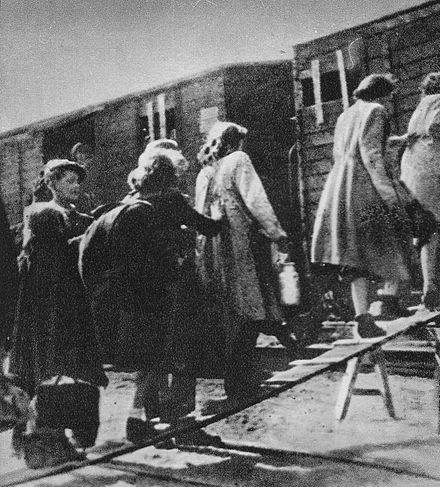 Jewish people, forcibly displaced by the Nazi regime during Germany's WWII occupation of Poland, loaded onto trains for transport to concentration camps. Umschlagplatz in Warsaw August 1942.jpg