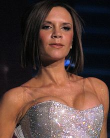 A close-up of a woman with short brown hair and a strapless glittery bustier.