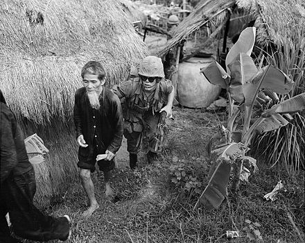 A Marine from 1st Battalion, 3rd Marines, moves a suspected Viet Cong during a search and clear operation held by the battalion 15 miles (24 km) west of Da Nang Air Base, 1965. Vietcongsuspect.jpg