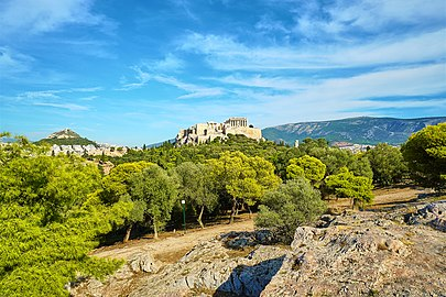 View of the Acropolis from the Hill of Pnyx. On the left Mount Lycabettus and on the right Mount Hymettus.jpg
