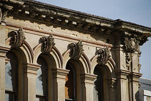 Oamaru stone - Weathered cornice and decorated keystones in the harbour area of Oamaru.