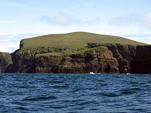 A green hill ends in dark brown cliffs over blue water.