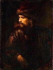 Ein Herr mit roter Pelzmütze im Lehnstuhl