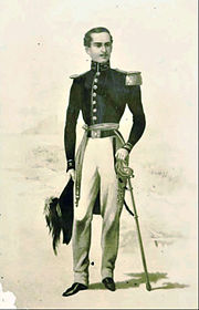 Printed full-length drawing of a thin young man standing and wearing a military tunic with an epaulet on the left shoulder, white trousers and his left hand resting on the hilt of a sword worn at the waist and his right hand holding a plumed hat