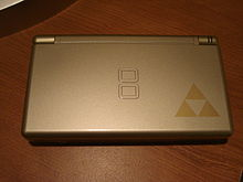 A gray handheld video game device with the Triforce logo in the bottom-right corner, which looks like three triangles touching at their points.